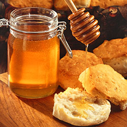 Jar of honey with honey dipping stick pouring honey on a biscuit.