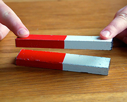 Image showing someone trying to hold a magnet down, but it is repulsed away from another magnet.