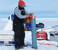 A researcher uses a drill to extract an ice core.