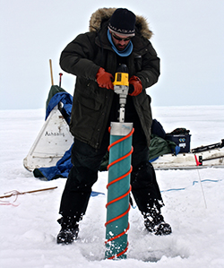 Researcher drills an ice core