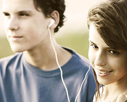 Teenagers sharing music through earbuds