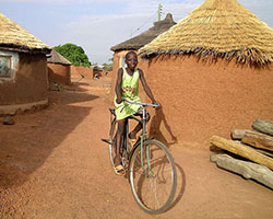 Child bicycling through village