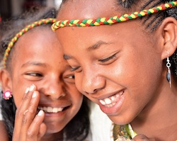 One Ethiopian girl whispering into the ear of another