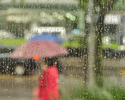 rain on a window with blurred people and umbrellas in the background