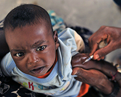 A young child receiving a vaccination through an arm injection.