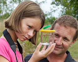 Young girl and older man show interest in an insect