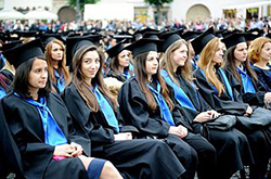 A row of female students sit at what appears to be a graduation ceremony. They each wear black robes and hats, with blue ties around their shoulders. One student looks at the camera, while the others have their gaze on the right side of the picture.