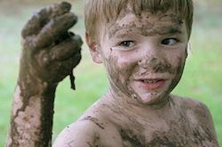 A kid with brown hair is covered in mud. We can see him from the shoulders up, and he is holding a dirty hand out in front of him. It looks like he has just crawled through the mud to find and hold up a worm.
