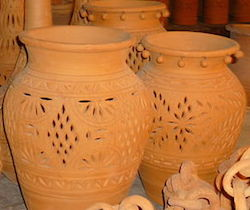 Two decorated clay pots sit in front of many others. They are orange-brown in color, and their decorated with an artistic design of small holes.