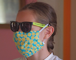 Girl wearing a colorful, protective mask, and sunglasses
