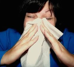 a woman's face close up. Her bangs fall in her face as she pushes her face in to a tissue. She holds the tissue to her face with both hands. She may be sneezing, or just blowing her nose.