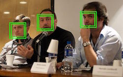 3 men are sitting at a table, but not looking toward the camera. Drinks and name badges rest on the table in front of them. Green boxes also sit on top of their faces, suggesting facial recognition process is occurring