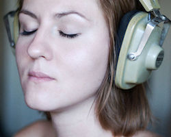 A girl is with medium length brown hair is wearing an old pair of headphones. She has her eyes closed and appears to be relaxing to the sound of the music