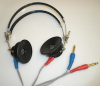 A pair of large black headphones with the cord raveled up to the right of them