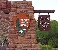 This is the sign for the National Park service headquarters at Zion National Park. The sign is in the shape of a brown arrowhead, resting on a tall thin brick structure.