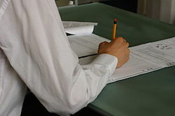 You see the arm of a person wearing a white dress shirt. They are sitting at a table holding a pencil. The paper they are working on is blurry, but it appears that they are reading through a test and filling in their answers on a scantron sheet.