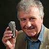 Paleontologist Richard Fortey holding trilobite fossil.