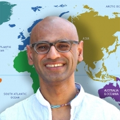 Arvind Varsani in front of a world map.