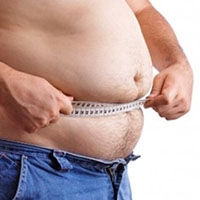 Obese man measuring waist