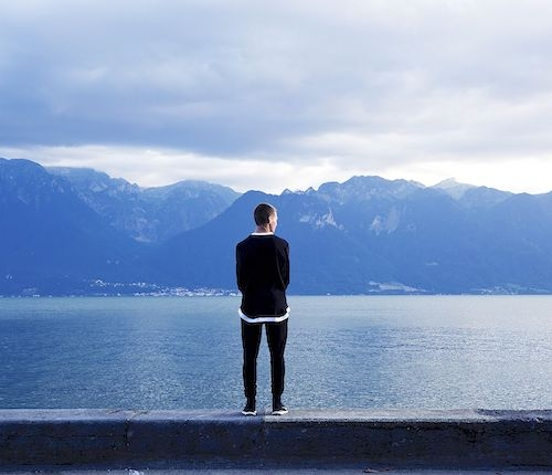 A man looking out over blue lake