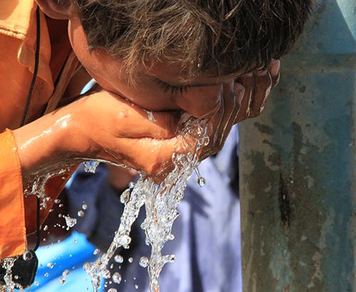un niño bebiendo agua