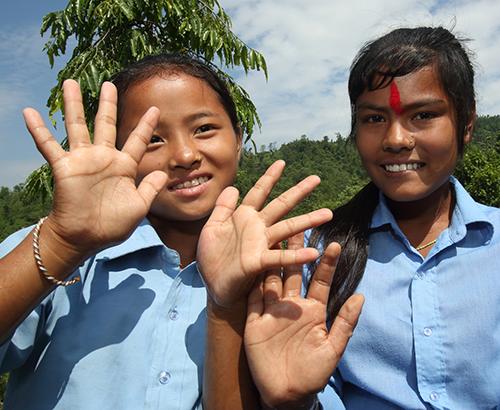 Dos niñas muestran sus manos limpias
