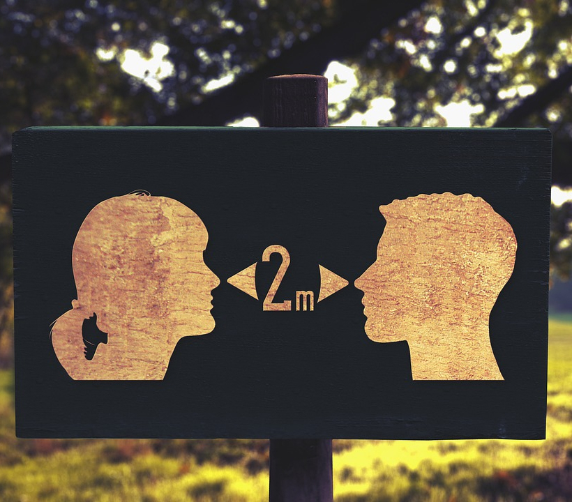 A sign for social distancing at a park, showing two people's faces, with a measurement of 2m recommended between them.