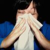 This is a picture of a woman using two hands to hold a tissue against her face.
